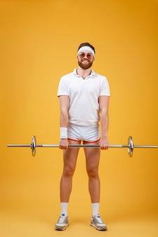 陽気な若いスポーツマンはバーベルでスポーツ演習を行います