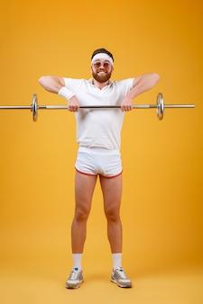 幸せな若いスポーツマンはバーベルでスポーツ演習を行います