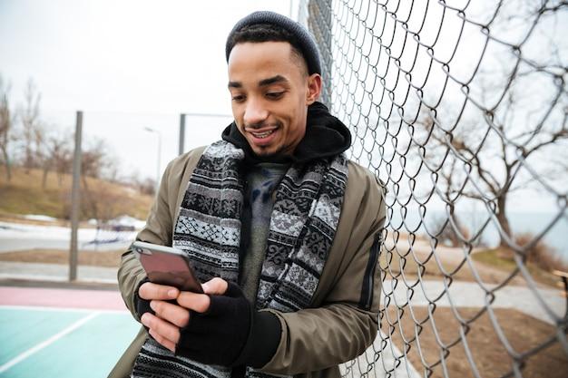 Счастливый афро-американский молодой человек, с помощью мобильного телефона на открытом воздухе