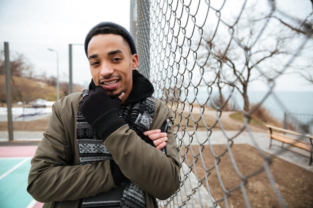 思いやりのあるアフリカ系アメリカ人の若い男が立っていると屋外で考える
