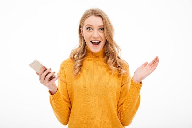 Удивлен молодая женщина, с помощью мобильного телефона.