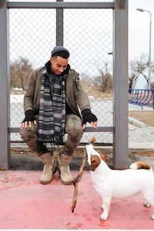 Счастливый афро-американский молодой человек, играя с собакой на открытом воздухе
