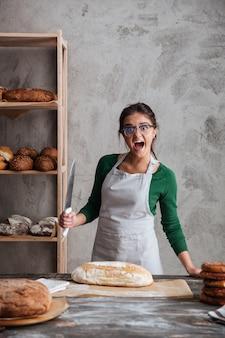 Кричащая молодая леди-пекарь нарезала хлеб.