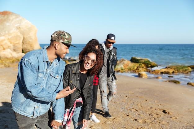 ビーチで野外を歩いている笑顔のアフリカの愛情のあるカップル