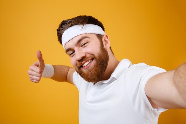 Улыбающийся спортсмен делает селфи и показывает большой палец вверх