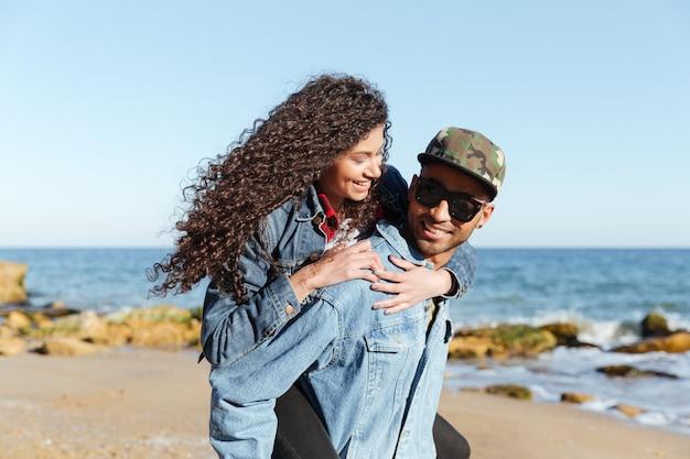 ビーチで野外を歩いている幸せなアフリカの愛情のあるカップル