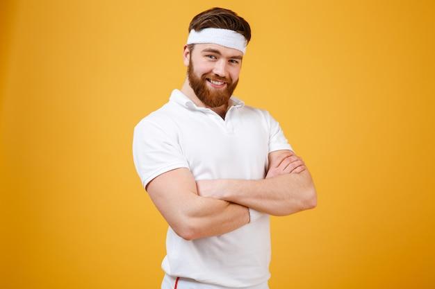 組んだ腕を持つスポーツマンの笑顔