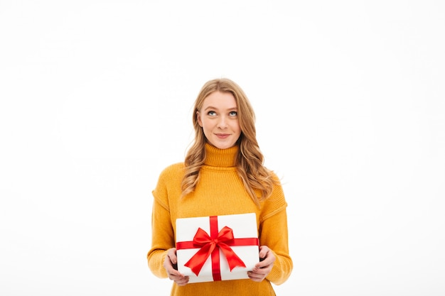 Милая веселая молодая женщина, держащая сюрприз подарочной коробке.