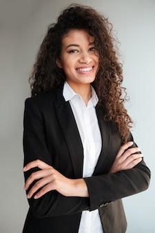 灰色の背景の上に立っているアフリカのビジネス女性。