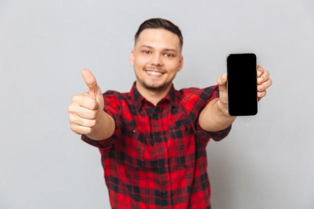 空白の画面の携帯電話を保持している幸せな笑みを浮かべてカジュアルな男