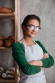 Концентрированный молодой леди пекарь, стоя со скрещенными руками