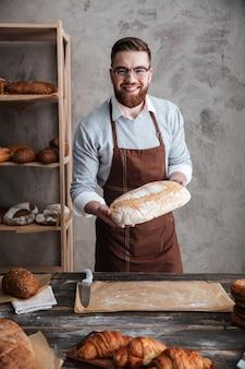 陽気な若い男のパン屋のパンを保持しているベーカリーに立っています。