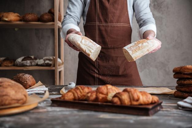 Подрезанное фото хлебопека молодого человека держа хлеб.
