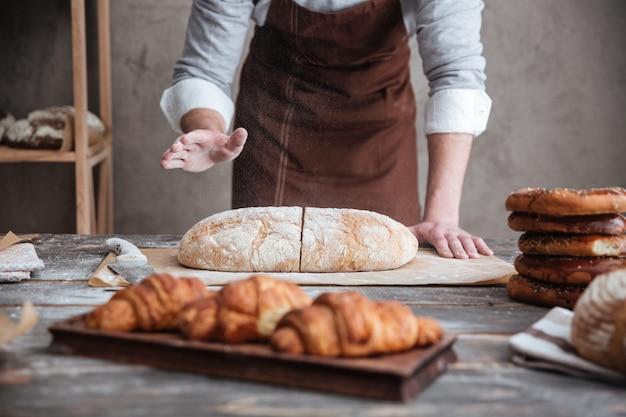 Молодой человек пекарь нарезать хлеб.