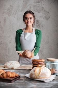 陽気な女性パン屋立ち、パンを保持
