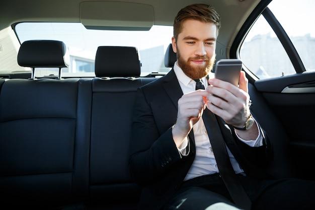 彼の手で携帯電話を見てスーツを着た男