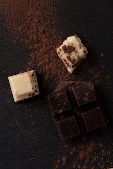 Вид сверху белых и темных разбитых плиток шоколада