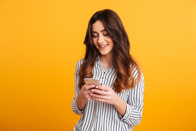 Портрет улыбающейся молодой девушки с помощью мобильного телефона