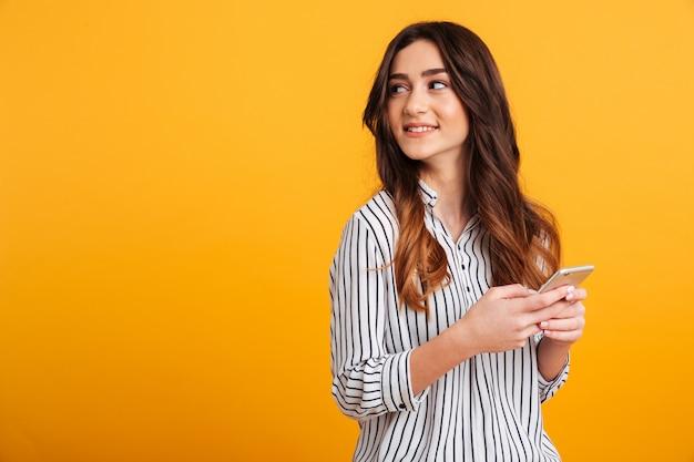 Портрет довольно молодая девушка держит мобильный телефон