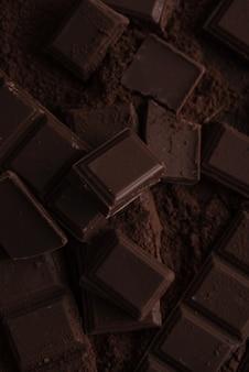 Кусочки плитки темного шоколада в шоколадной пудре