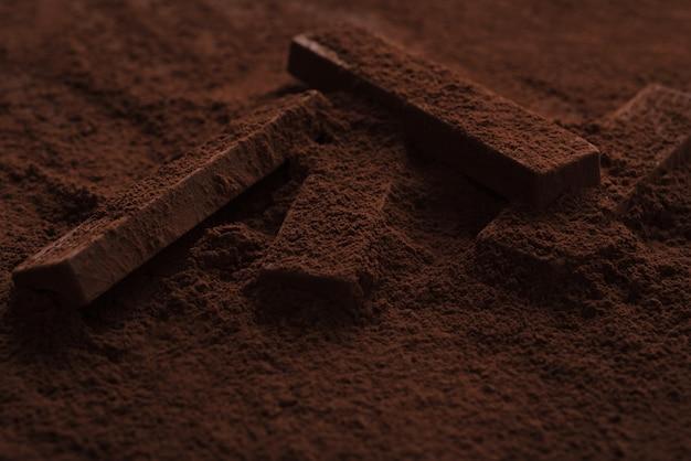 Крупный план вкусных кусочков шоколада, лежащих в шоколадной пудре