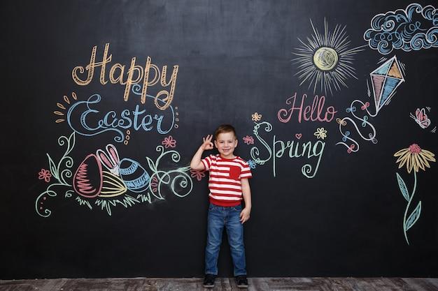 Улыбающийся счастливый маленький мальчик, стоя и показывая
