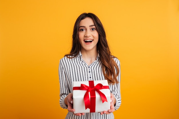 Жизнерадостная брюнетка женщина в рубашке, держа подарочной коробке