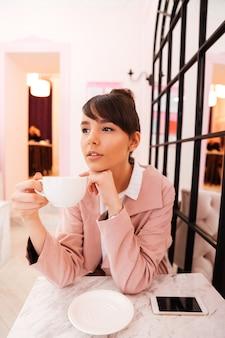 一杯のコーヒーを保持している若い魅力的な女性の肖像画