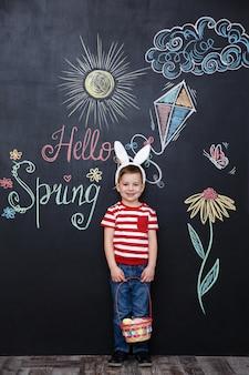 Счастливый маленький мальчик носить уши кролика и проведение пасхальной корзины
