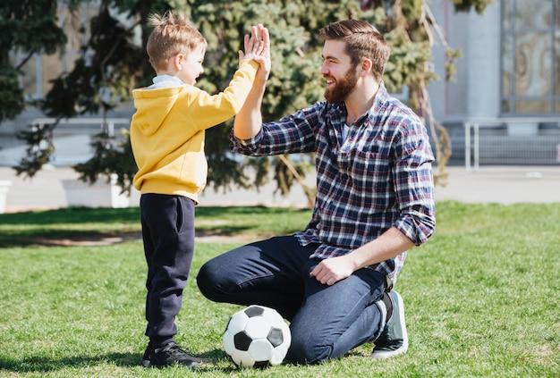 若い父親と彼の幼い息子がハイファイブを与える