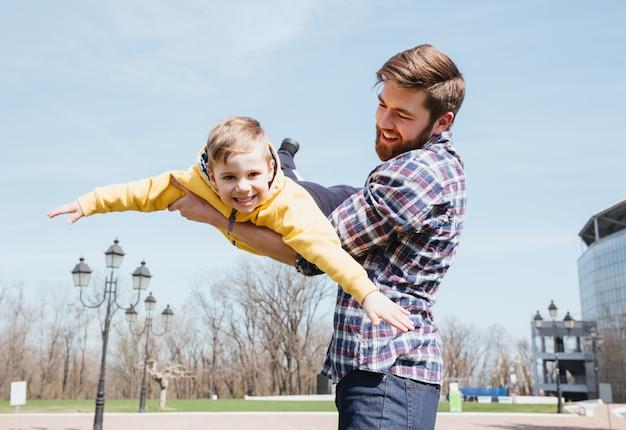 父と彼の幼い息子が公園で一緒に遊んで