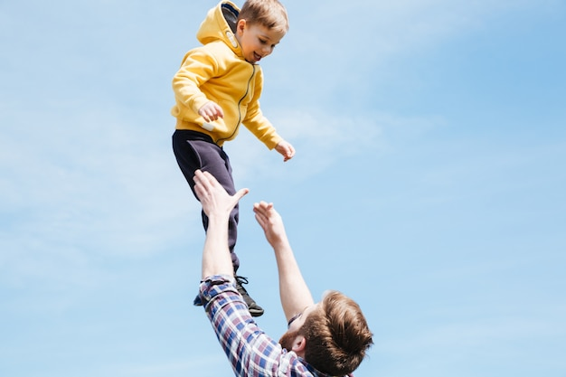 父と息子が都市公園で一緒に遊んで
