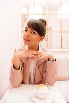 Улыбается молодая женщина, сидя в кафе с чашкой кофе