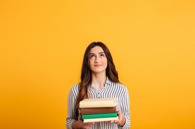 Улыбаясь брюнетка женщина в рубашке, держа книги и глядя вверх