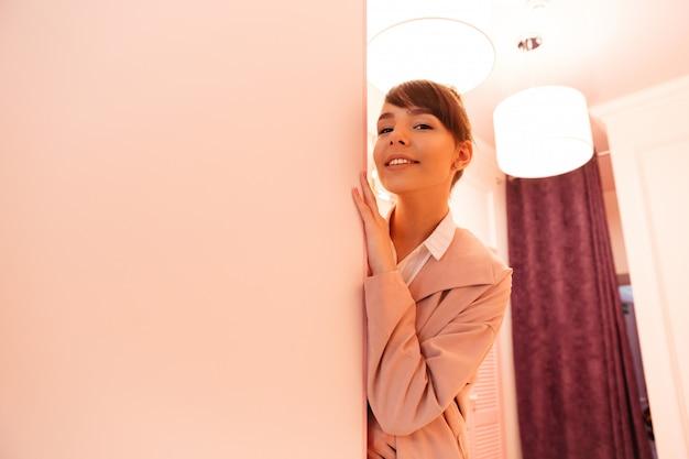 Улыбается молодая женщина в пальто, опираясь на стену