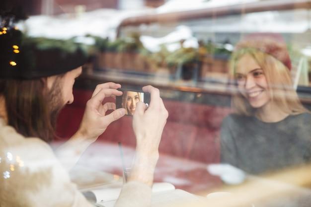 Портрет счастливой пары в кафе за стеклом