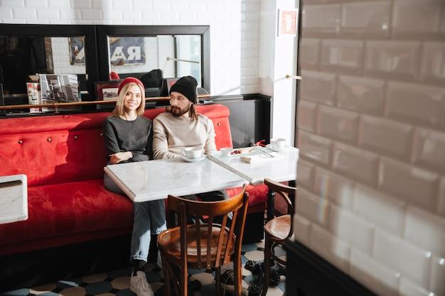 Пара в кафе с зеркалом позади
