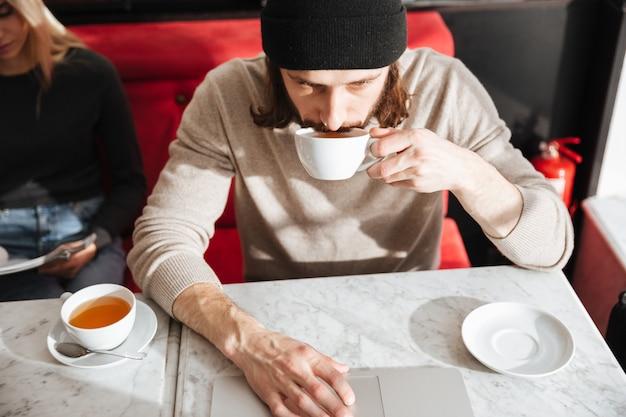Мужчина пьет кофе возле подруги