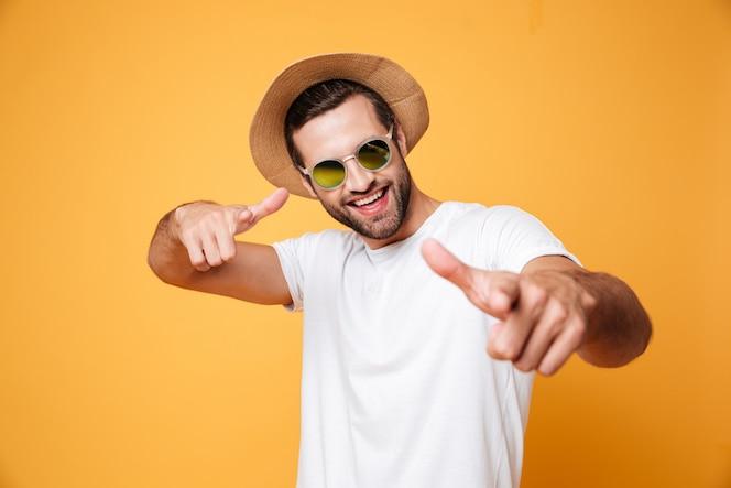 オレンジ色の壁を越えて立っている陽気な若い男