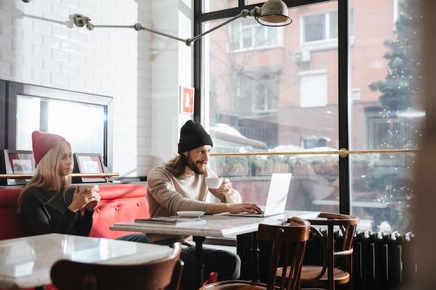 Вид сбоку мужчина с ноутбуком возле подруги