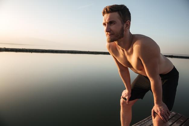 ビーチに立っている若いスポーツマンを集中