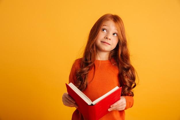 Думая маленькая рыжая девушка читает книгу