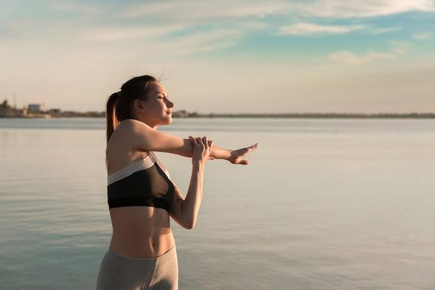ビーチで若いスポーツ女性はストレッチ体操を行います。