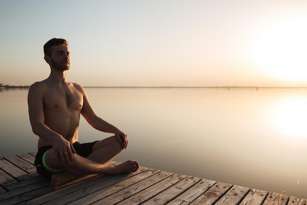 集中して若いスポーツマンはヨガ瞑想の練習をします