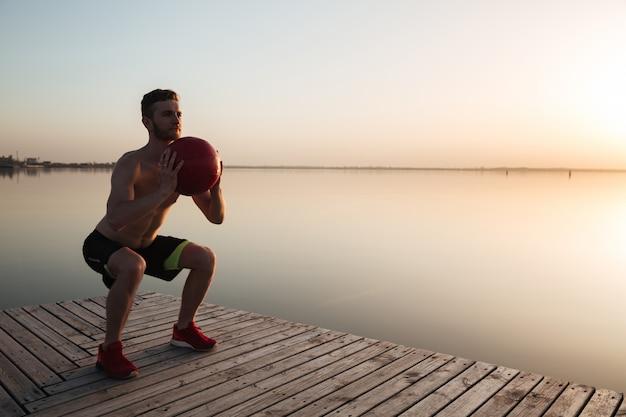 Красивый молодой спортсмен делает спортивные упражнения