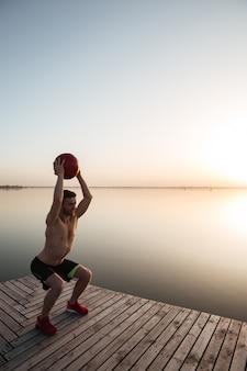 Серьезный молодой спортсмен делает спортивные упражнения с мячом