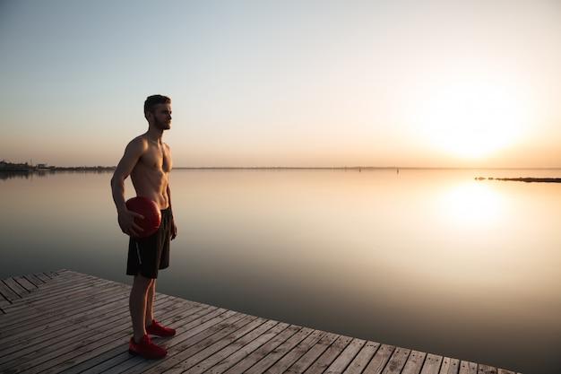 Серьезный молодой спортсмен стоя с шариком на пляже.