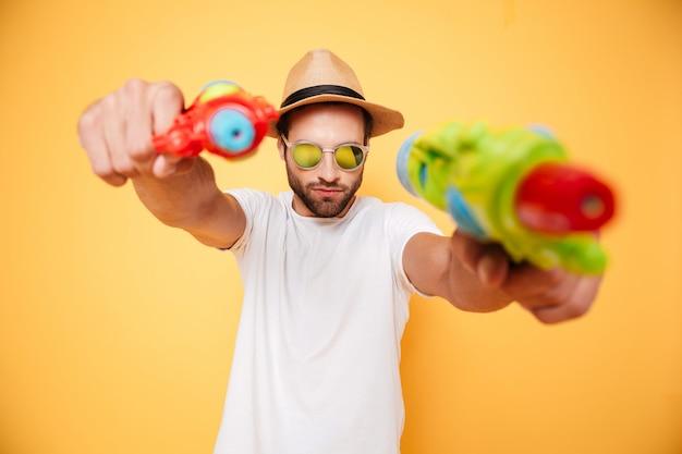 Серьезный молодой человек держит игрушечные водяные пистолеты