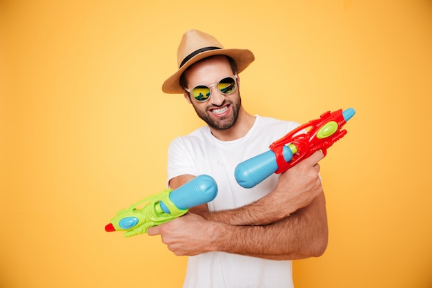 Счастливый молодой человек держит игрушечные водяные пистолеты