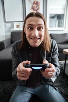 Счастливый человек сидит дома в помещении играть в игры